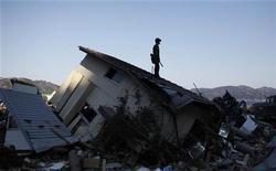 <p>Спасатель стоит на крыше разрушенного дома в поселке Ямада, 5 апреля 2011 года. Землетрясение силой 7,4 балла по шкале Рихтера произошло на северо-востоке Японии поздно вечером в четверг, в районе объявлено предупреждение о цунами. REUTERS/Toru Hanai</p>