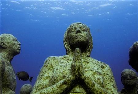 Figures are seen in an underwater sculpture park between Cancun and Isla Mujeres December 11, 2010. The sculptures created by British artist Jason de Caires Taylor used 'life casts' made from materials that encourage coral growth to build an underwater installation on the sea bed off the coast of Cancun Mexico. REUTERS/Jorge Silva