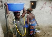 <p>Women draw water in Abidjan April 8, 2011. REUTERS/Thierry Gouegnon</p>