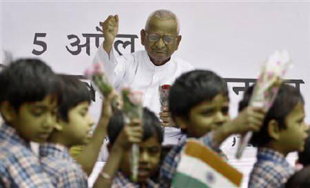 School children, holding the Indian national flag and flowers, walk past social activist Anna Hazare in support of a ''fast unto death'' campaign in New Delhi April 7, 2011. REUTERS/Parivartan Sharma
