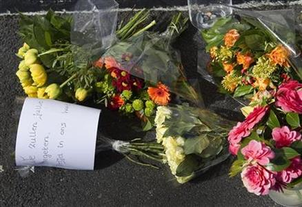 A note saying ''We will never forget you, forever in our heart'' accompanies the flowers laid at the shopping centre where a lone gunman killed six people in Alphen aan de Rijn April 10, 2011. REUTERS/Michael Kooren