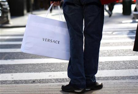 A shopper holds a bag from the high-end luxury goods maker Versace as he stands at a crosswalk along 5th Avenue in New York, November 19, 2008. REUTERS/Mike Segar