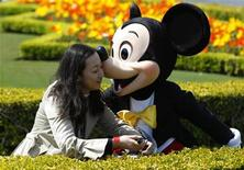 <p>A visitor is kissed by Disney character Mickey Mouse at Tokyo Disneyland in Urayasu, east of Tokyo April 15, 2011. REUTERS/Issei Kato</p>