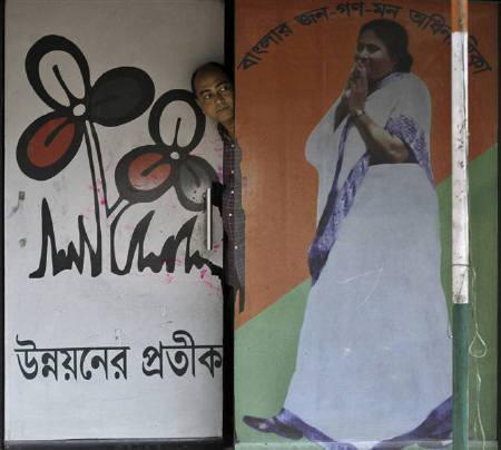 A man looks out from the door of Trinamool Congress party office with the door painted with a picture of Railways Minister and Trinamool Congress chief Mamata Banerjee, in Kolkata March 22, 2011. REUTERS/Rupak De Chowdhuri