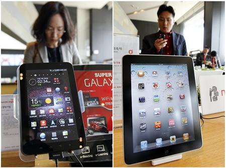 Customers look at smartphones behind Samsung Electronics' Galaxy Tab tablet (L) and Apple Inc's iPad tablet displayed at a registration desk at the headquarters of South Korean mobile carrier KT in Seoul, in this combination picture made April 19, 2011. Apple sued Samsung Electronics claiming the South Korean firm's Galaxy line of mobile phones and tablets ''slavishly'' copies the iPhone and iPad, according to court papers, a move analysts say is aimed at keeping its close rivals at bay. Samsung said it would respond to the legal action ''through appropriate legal measures to protect our intellectual property.'' REUTERS/Jo Yong-Hak