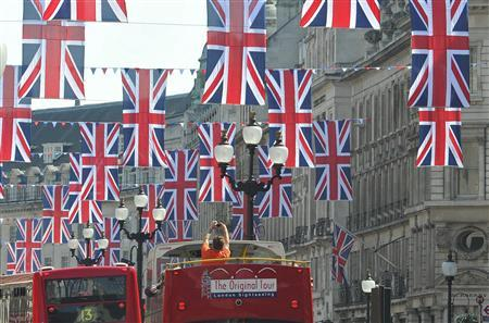 A tourist photographs Union flags hung along Regent Street in celebration of the forthcoming royal wedding, in London, April 19, 2011. REUTERS/Toby Melville