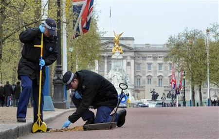 Metropolitan police officers carry out security checks on drains and lamp posts along the Mall ahead of the Royal wedding in London April 14, 2011. REUTERS/Anthony Devlin/POOL