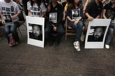 Artists and activists carry portraits of detained Chinese artist Ai Weiwei, urging for his release, outside the Chinese liaison office in Hong Kong April 17, 2011. REUTERS/Tyrone Siu