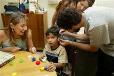 <p>Chilean couple Patricio Villablanca (R) and Helen Vega (standing C) work with a speech therapist (L) to prepare their 6-year-old deaf, dumb son, Dan Villablanca Vega, for his first experience at hearing after having a cochlear device surgically implanted nearly two months earlier, at the Naval Hospital in Vina del Mar, 112 kms west of Santiago, January 28, 2005. REUTERS/Eliseo Fernandez</p>