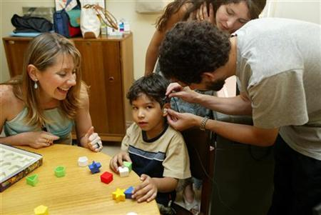 Chilean couple Patricio Villablanca (R) and Helen Vega (standing C) work with a speech therapist (L) to prepare their 6-year-old deaf, dumb son, Dan Villablanca Vega, for his first experience at hearing after having a cochlear device surgically implanted nearly two months earlier, at the Naval Hospital in Vina del Mar, 112 kms west of Santiago, January 28, 2005. REUTERS/Eliseo Fernandez