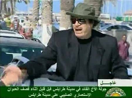 Libyan leader Muammar Gaddafi shakes hands with a man as he travels in a convoy through the streets of Tripoli in this still image taken from video April 14, 2011. REUTERS/Libyan State TV via Reuters TV