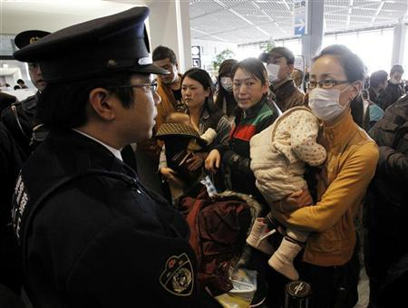Chinese tourists complain to a Japanese security guard (L) as they wait for their flights at Narita International Airport, east of Tokyo, March 19, 2011, eight days after an earthquake and tsunami hit Japan. REUTERS/Jo Yong-Hak