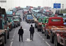 <p>People walk along an unfinished road being used by truck drivers to park their container trucks near a port in Shanghai April 21, 2011, following a protest nearby the area earlier in the morning. Truck drivers were planning a second REUTERS/Carlos Barria</p>