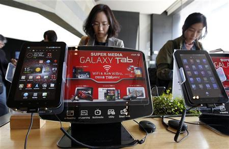 Customers look at smartphones behind Samsung Electronics' Galaxy Tab tablets on display at a registration desk at the headquarters of South Korean mobile carrier KT in Seoul April 19, 2011. REUTERS/Jo Yong-Hak