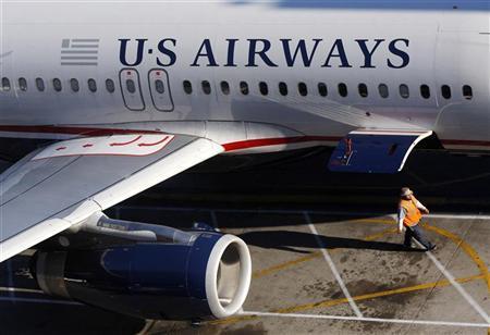 A ground crew worker walks past a U.S. Airways aircraft outside terminal 4 at Phoenix Sky Harbor International Airport in Phoenix, April 8, 2010. REUTERS/Joshua Lott