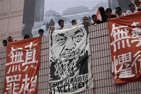 Artists hold banners including one featuring a portrait of detained Chinese artist Ai Weiwei during a protest urging for his release, in Hong Kong April 23, 2011. REUTERS/Tyrone Siu