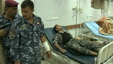A wounded policeman stands near another lying on a hospital bed in Baghdad April 24, 2011 in this still image taken from video. REUTERS/Reuters TV
