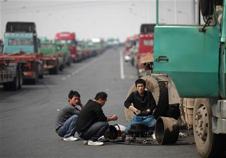 Truck drivers fix a container truck at an unfinished road being used by truck drivers to park their container trucks near a port in Shanghai, April 23, 2011. REUTERS/Carlos Barria