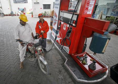 A worker pumps petrol into a customer's motorcycle at a fuel station in Karachi March 1, 2011. REUTERS/Akhtar Soomro