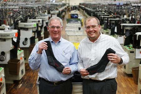 Wigwam Chairman and CEO Bob Chesebro (L) and President and COO Jerry Vogel pose with their socks on the factory in Sheboygan, Wisconsin, January 28, 2011. China's rise as a manufacturing power has benefited American factory owners in at least one way. The Middle Kingdom's insatiable appetite for second-hand machinery means that small U.S. businesses can make a quick buck by selling old equipment there. But Chesebro refuses to surrender his edge. His equipment ends its days as scrap metal in a dumpster behind his plant. In several ways, Wigwam defies the conventional wisdom of today's global market. Picture taken January 28. REUTERS/John Gress