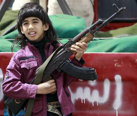 The son of a rebel fighter holds his father's weapon at the front line along the western entrance of Ajdabiyah April 28, 2011. REUTERS/Amr Abdallah Dalsh