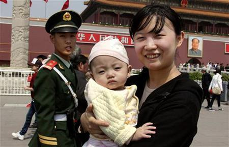 A paramilitary policeman yells at a woman holding her baby as she stands next to the portrait of the former Chariman Mao Zedong in Tiananmen Square in Beijing April 28, 2011. China's mainland population grew to 1.339 billion by 2010, according to census figures released on Thursday, up 5.9 percent from the 1.265 billion at the last census in 2000, and lower than the 1.4 billion population some demographers had projected for the latest count. The Chinese government's strict controls on family size, including a one-child policy for most urban families, have brought down annual population growth to below 1 percent and the rate is projected to turn negative in coming decades. China's choke on family size to usually one child in cities and two in the countryside now threatens its economic future, many demographers have said, with fewer people left to pay and care for an increasingly graying population. REUTERS/David Gray