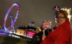 <p>A woman holding the British flag smiles as she stands on a bridge next to the illuminated London Eye in London late evening April 28, 2011. REUTERS/Kai Pfaffenbach</p>