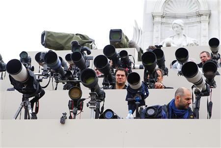 Members of the media point their lenses towards Buckingham Palace as they wait on the Queen Victoria Memorial in London April 29, 2011. REUTERS/Chris Ison/Pool