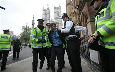 A man is restrained by police officers outside Westminster Abbey before the wedding between Britain's Prince William and Kate Middleton, in London April 29, 2011. REUTERS/Suzanne Plunkett