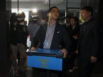 <p>Un policier quitte les bureaux de Google à Séoul en emportant des éléments saisis lors d'une perquisition menée mardi dans le cadre d'une enquête sur sa filiale de publicité pour mobiles AdMob, soupçonnée d'avoir recueilli illégalement des données de géolocalisation. /Photo prise le 3 mai 2011/REUTERS/Truth Leem</p>