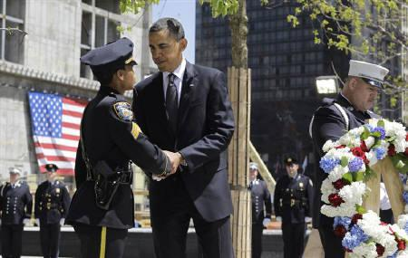 U.S. President Barack Obama shakes the hand of a New York City police officer after placing a wreath at the World Trade Center site in New York, May 5, 2011. REUTERS/Kevin Lamarque