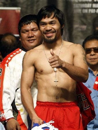 Manny Pacquiao of the Philippines gives a ''thumbs-up'' to a member of the audience during an official weigh-in at the MGM Grand Garden Arena in Las Vegas, Nevada May 6, 2011. Filipino trainer Buboy Fernandez is at left. REUTERS/Steve Marcus