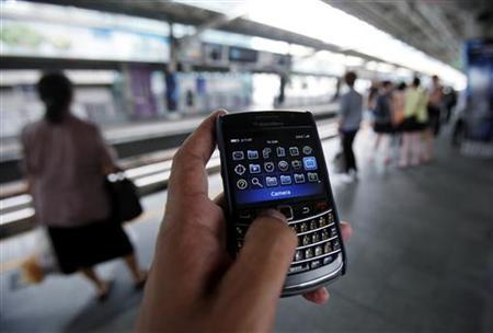 A man uses his mobile phone as he waits for a skytrain in Bangkok September 23, 2010. REUTERS/Chaiwat Subprasom