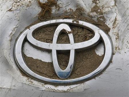 A Toyota logo on a damaged car is seen at a dump site for tsunami debris near Sendai airport March 30, 2011. REUTERS/Kim Kyung-Hoon