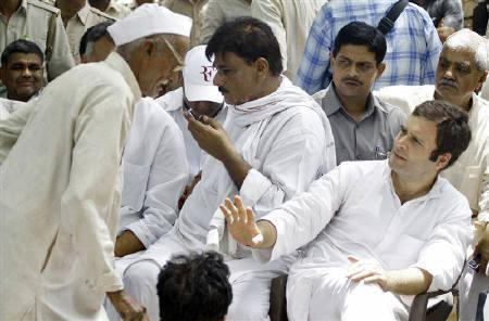 Rahul Gandhi (R), Member of Parliament and son of ruling Congress party chief Sonia Gandhi, gestures to a villager during his visit to Parsaul village after Saturday's clash between farmers and police in Gautam Buddha Nagar district of Uttar Pradesh May 11, 2011. REUTERS/Parivartan Sharma