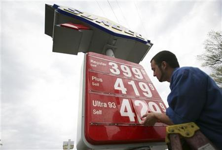An employee changes gas prices on a sign at a Sunoco station in Alexandria, Virginia, April 12, 2011. REUTERS/Molly Riley