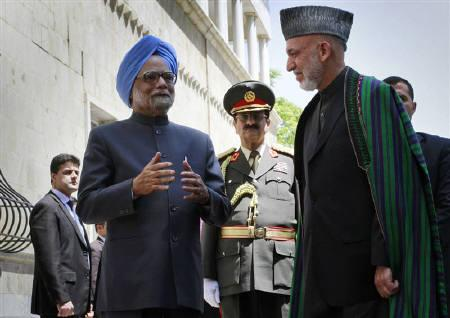 Afghanistan's President Hamid Karzai (R) speaks with Prime Minister Manmohan Singh (C) at the presidential palace in Kabul May 12, 2011.  REUTERS/Musadeq Sadeq/Pool