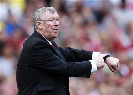 Manchester United manager Alex Ferguson points to his watch during his team's English Premier League soccer match against Arsenal at the Emirates stadium in north London, May 1, 2011. REUTERS/Eddie Keogh