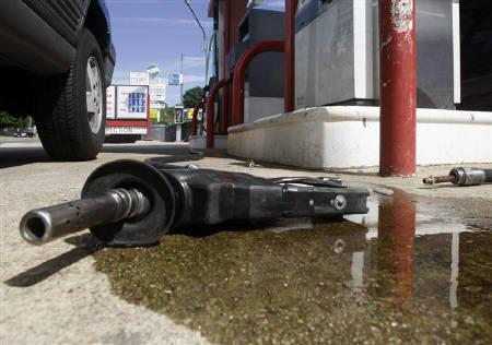 A fuel pump nozzle lays in a puddle of gasoline after it was disconnected from the hose at a station in Arlington, Virginia, June 11, 2008.   REUTERS/Jim Young/Files