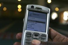 <p>A man scrolls through his mobile phone to carry out a money transaction via M-PESA in Nairobi May 12, 2009. REUTERS/Noor Khamis</p>