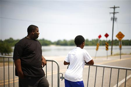 Jabari Singleton (L) and Wanya Brown watch as floodwaters rise in Melville, Louisiana May 15, 2011. REUTERS/Eric Thayer