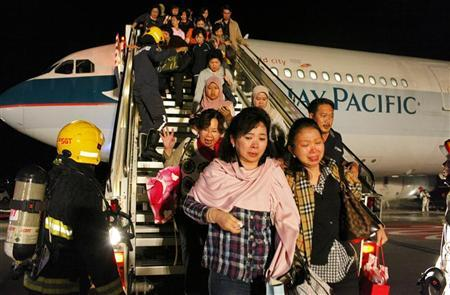 Passengers on Cathay Pacific flight CX715 disembark from the aeroplane after it landed safely at Changi Airport in Singapore May 16, 2011. REUTERS/Beawiharta