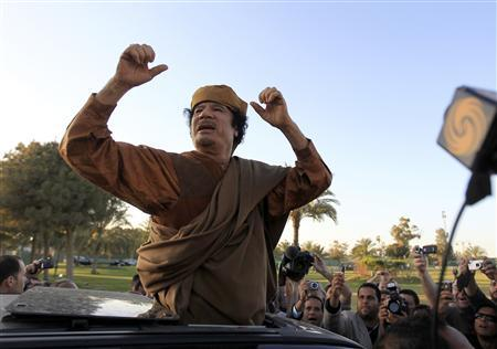 Libyan leader Muammar Gaddafi cheers his supporters after a meeting with a delegation of five African leaders at his Bab al-Aziziyah compound in Tripoli, April 10, 2011. REUTERS/Zohra Bensemra