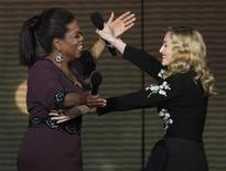"""<p>Oprah Winfrey and Madonna embrace during the taping of """"Oprah's Surprise Spectacular"""" in Chicago May 17, 2011. REUTERS/John Gress</p>"""