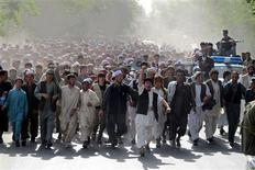 <p>Afghans chant slogans as they protest the killing of four people overnight after a raid by NATO and Afghan forces, in Taloqan May 18, 2011. REUTERS/Stringer</p>