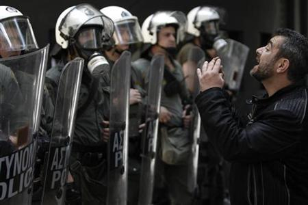 A municipal worker gestures in front of riot policemen during a march against austerity in Athens, May 18 2011. REUTERS/John Kolesidis