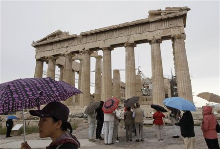 Tourists holding umbrellas stand in front of the temple of the Parthenon at the Acropolis hill in Athens, May 19 2011. REUTERS/John Kolesidis