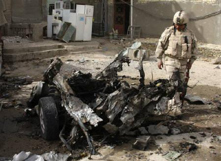 A soldier inspects the remains of a vehicle used in a bomb attack in Baghdad's Sadr city May 22, 2011. REUTERS/Kareem Raheem