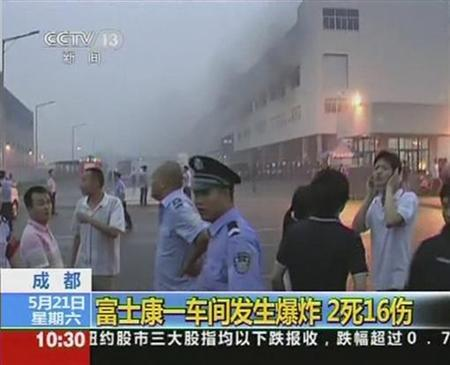 Smoke rises as police and onlookers stand near at a Foxconn factory in Chengdu, Sichuan province, May 20, 2011 in this still image taken from a video grab. REUTERS/CCTV via Reuters TV