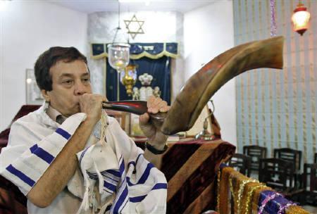 Ezekiel Isaac Malekar, honorary secretary of the Judah Hyam Synagogue synagogue, poses with a shofar horn inside the synagogue in New Delhi May 20, 2011. REUTERS/B Mathur